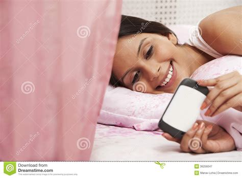 smiling girl using mobile phone in bed royalty free stock woman text messaging on a mobile phone on the bed royalty