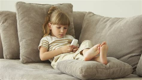 little girl couches little girl lying on sofa with tablet and smiling stock