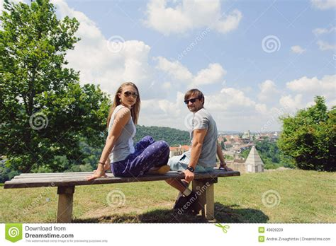 couple sitting on bench young couple on bench