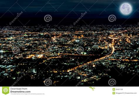 lights of city in time with blue moon stock