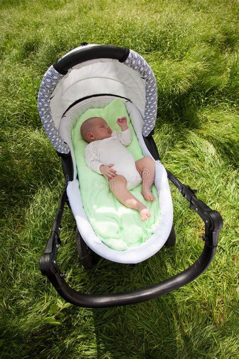 neonato nella neonato dorme nella carrozzina all aperto fotografie