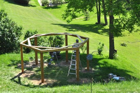 diy hanging pit drives 6 posts into the ground in his backyard to