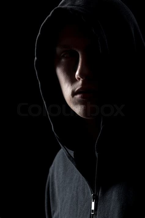 man in the dark portrait of mysterious man in hoodie in the dark dangerous criminal scarcely visible in the