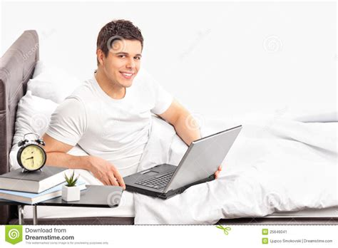 working from bed man lying on a bed and working on a laptop stock image
