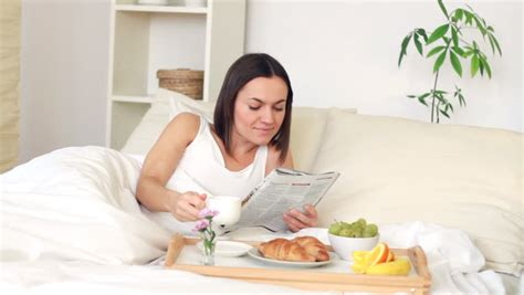 eating in bed woman eating breakfast in bed and reading magazine stock