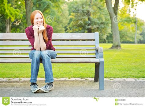 waiting on a bench a woman waiting on a bench in a park stock image image
