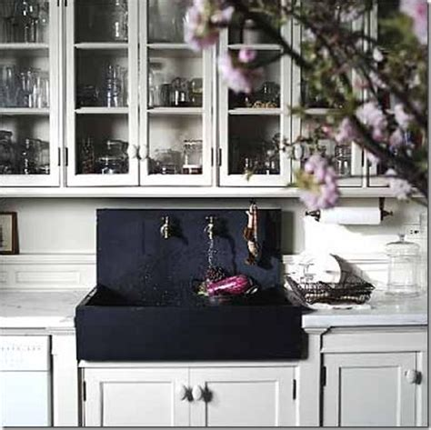 black farmhouse sink in classic white kitchen and