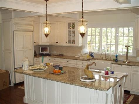 Brown Countertops White Cabinets by Painted White Kitchen With Paneled Refridgerator And