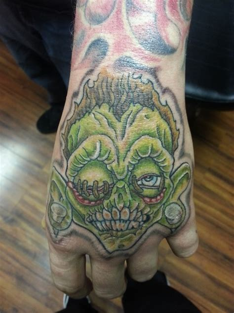 shrunken heads tattoo green ink shrunken on left