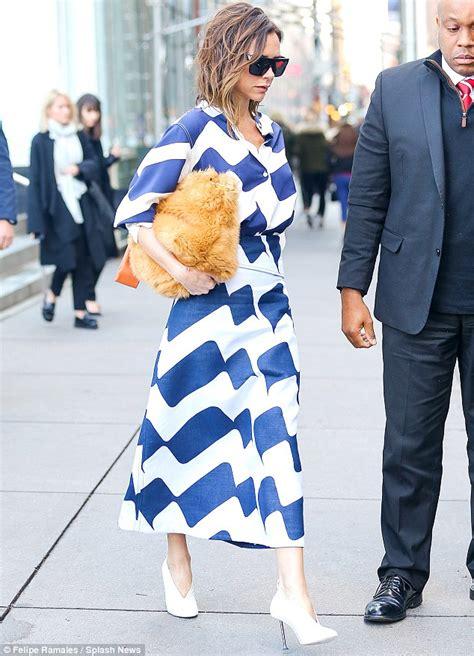 Mrs Beckham Looks Cool In by Beckham Cradles A Bright Orange Bag She