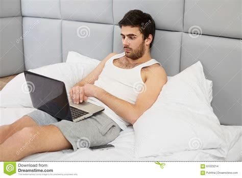 working in bed man working with computer in bed stock photo image of