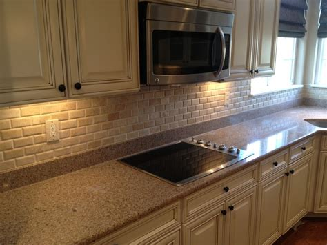 French Kitchen Cabinet by Travertine Backsplash