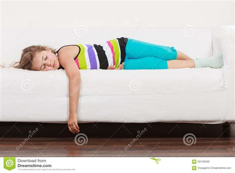 lying on a sofa tired exhausted lazy little girl kid lying on sofa stock