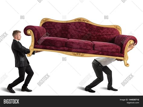 couch for men men carrying a very heavy antique sofa stock photo stock