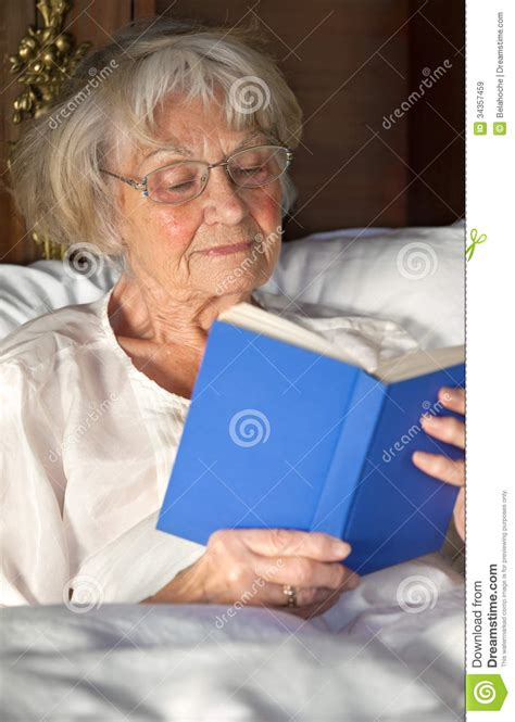 read comfortably elderly pensioner reading a book in bed royalty free stock