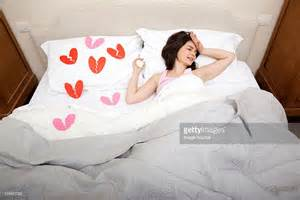 crying in bed woman crying in bed with broken heart shapes on bedclothes stock photo getty images