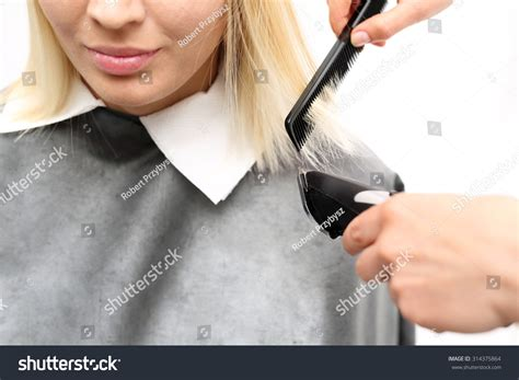 woman cuts hair with fork and clippers woman cuts hair with fork and clippers cutting hair