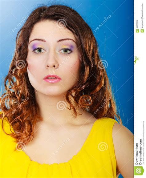 curling hair towards the face closeup woman face long curly hair portrait stock photo