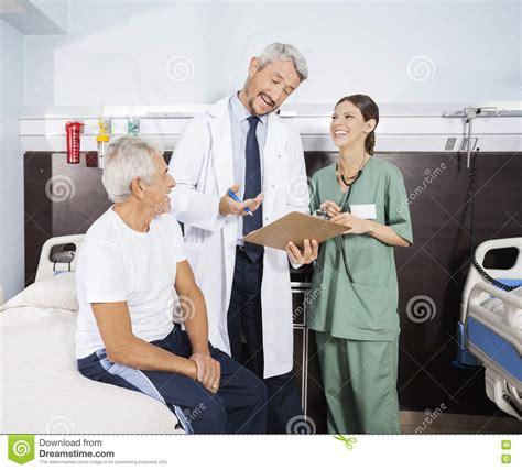 Rehab Doctors - happy doctor explaining report to senior patient in rehab