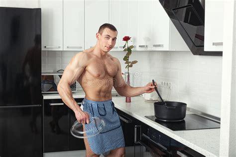 bodybuilder in de keuken dichtbij fornuis stock foto