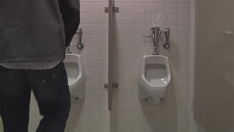 male public bathroom man using the urinal in a public restroom stock footage