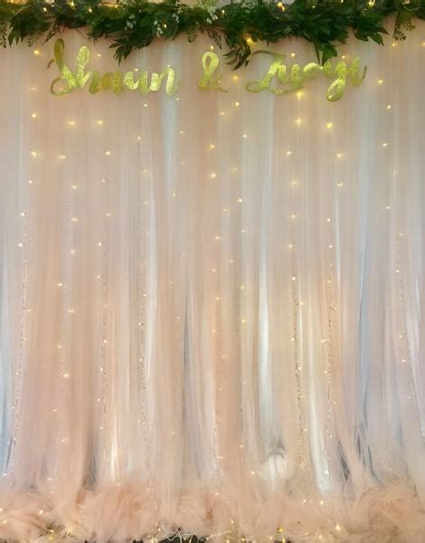 Blush tulle backdrop with artificial foliage and fairy