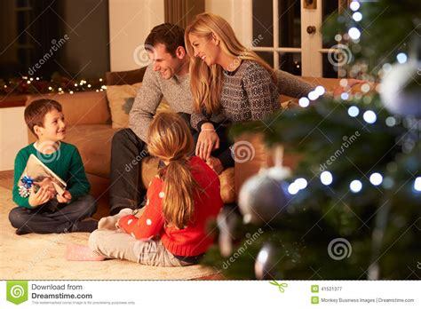 family exchanging gifts by christmas tree stock image