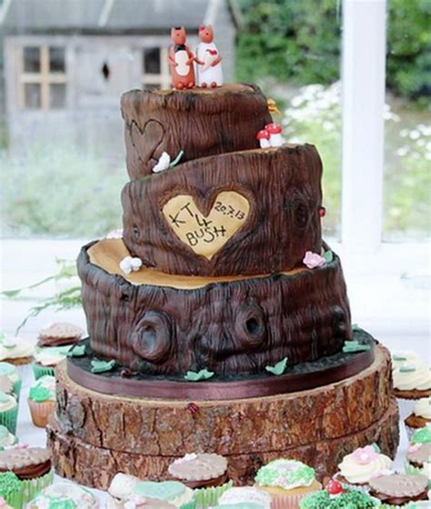 tree theme wedding cake in 3 tiers with carved hearts animal groom toppers and cupcakes