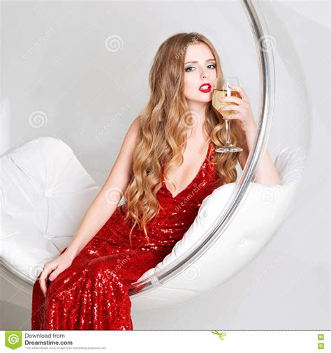 blonde bob red dress young blonde woman in red dress holding a glass of white