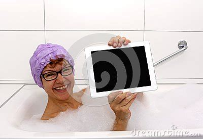mature bathtub enthusiastic mature woman in bathtub with tablet computers