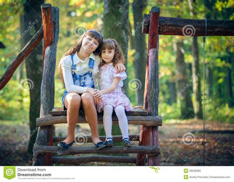 swinging sister little sisters on swing in park royalty free stock photo