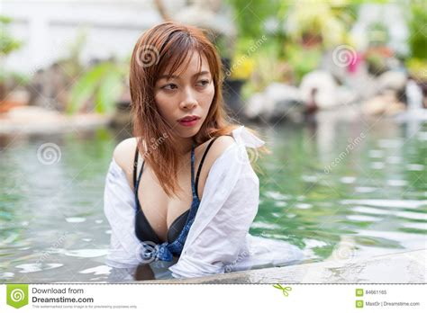 little young girl paradise asian woman in hotel swimming pool relaxing vacation