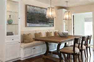 a built in banquette is flanked by glass cabinets for
