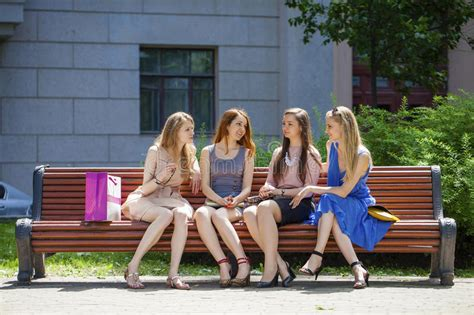 park bench group group of four young women sitting on bench in summer park