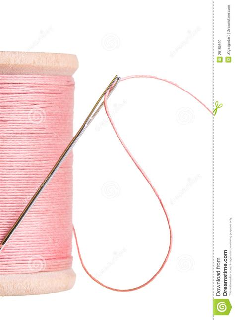 String With Needle And Thread - spool of pink sewing thread with needle stock photo