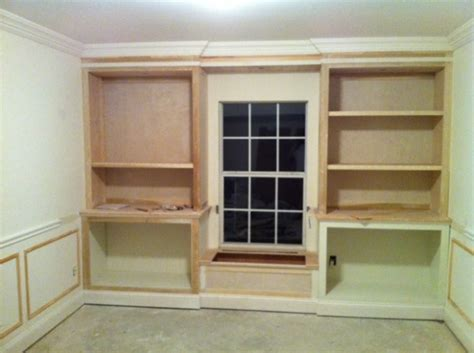 Lower cabinets / upper bookcases flanking window seat