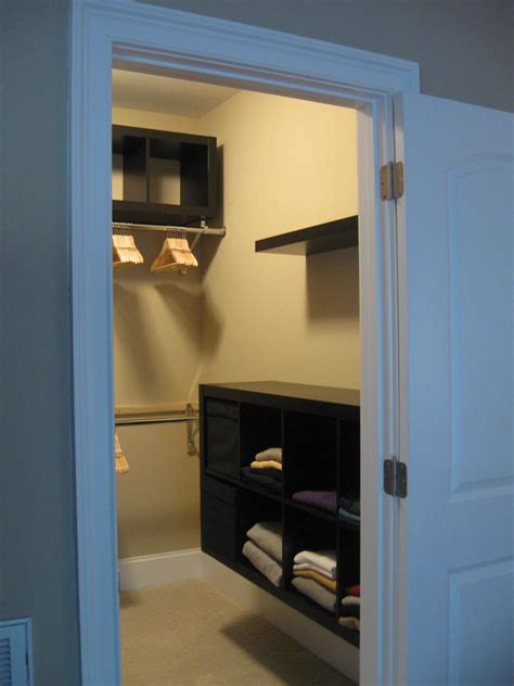 interior small walk in closet with wire hanging shelves and clothes rack underneath cool