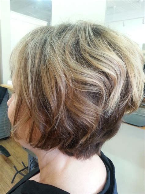 black stacked bob with purple balayage balayage highlights on a stacked bob cut and color by