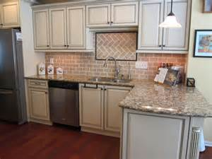 this is a compact kitchen with a traditional cabinet design which uses kitchen tile backsplash ideas with cream cabinets