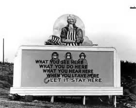 Uncle sam and see hear speak monkeys for secrecy on billboard in oak