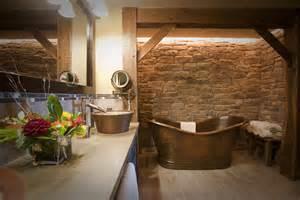 a stone wall backs the tub in the big thunder suite master earth tone bathroom designs bathroom tone mason jar dreams