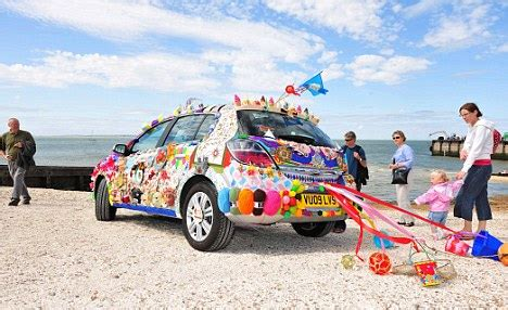 artistic duo decorate car with travel trinkets to create