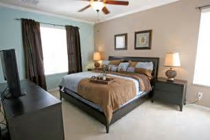 Master bedroom with pin and blue color scheme and dark wood furniture