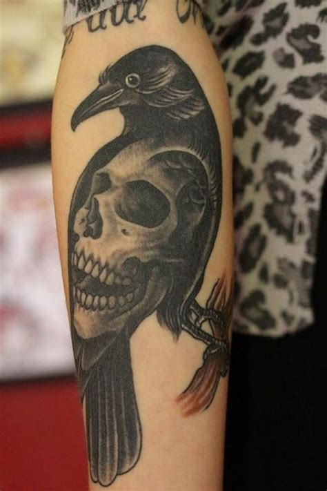 black crow tattoo black on branch stylized with big human skull
