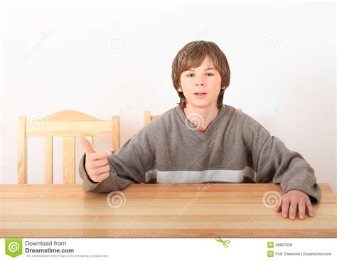 boy sitting wooden table stock photo image 48807958