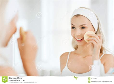 bathroom facials young woman washing face with sponge at bathroom stock