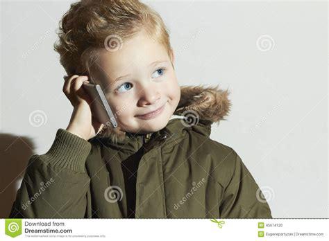 Coat Modern Kid boy talking on the cellphone modern child in winter coat fashion children stock
