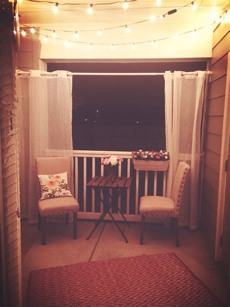 small apartment patio with lights strung at
