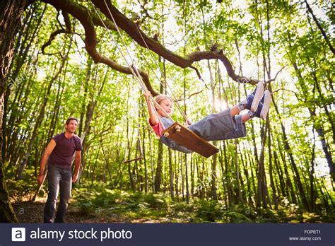 forest swing father pushing daughter on rope swing in forest stock