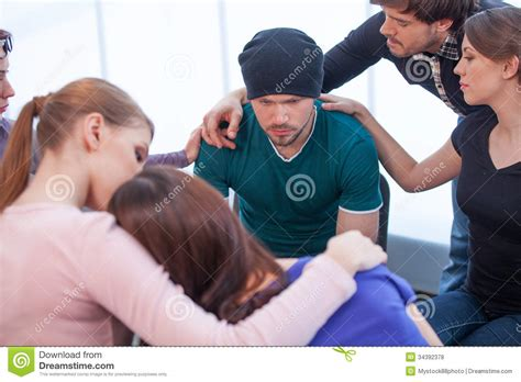 how to comfort a guy several people comforting young man on background royalty